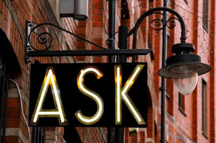 """A lit up sign post saying """"ASK"""" reminding people to ask questions"""