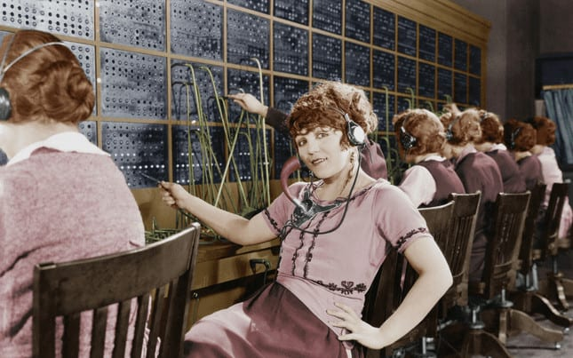Woman sitting at telephone switch board determining who is calling: spirit or ego