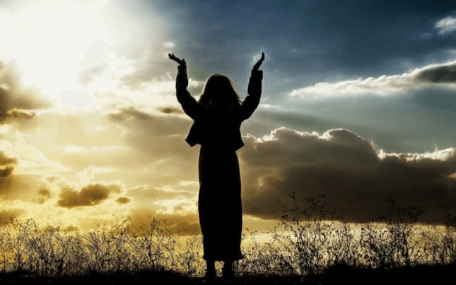 Woman in nature with hands lifted in the air, spirit is calling her