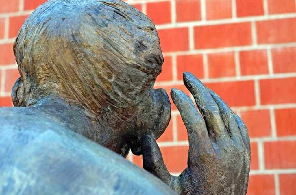 Statue of a man with his hand to his ear as he listens to spirit